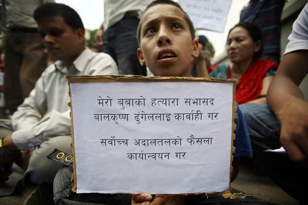 Bikash Shrestha, 13, who lost his father during Nepal's civil war sits at a protest demanding justice for the killings of loved ones. Kathmandu June 6, 2011. REUTERS/Navesh Chitrakar