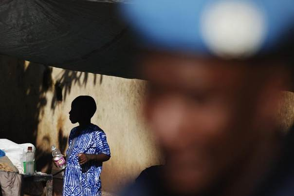 A boy stands near a UN peacekeeper from Senegal on patrol in Bamako, Mali, August 22, 2013. REUTERS/Joe Penney