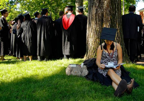 Graduating student Jennifer Lim sits in the shade before the start of the 361st Commencement Exercises at Harvard University in Cambridge, Massachusetts on May 24, 2012. REUTERS/Brian Snyder