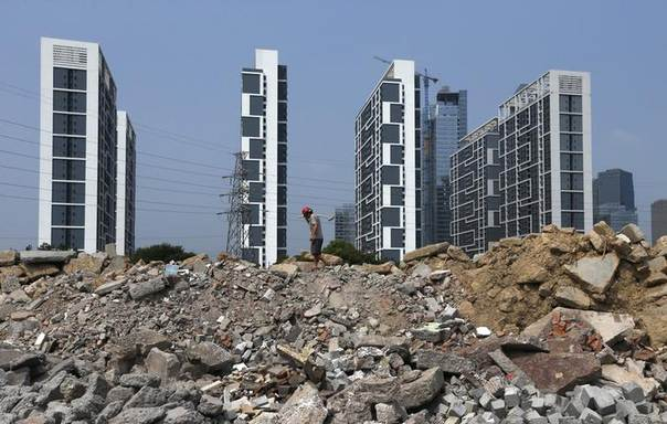A labourer works at a construction site in front of newly built residential buildings in Yongkang, Zhejiang province, August 6, 2014. REUTERS/William Hong