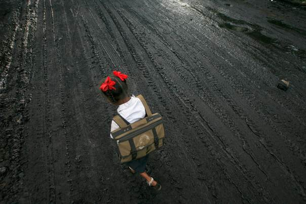 In a file photo from 2009, a schoolgirl walks on a road covered with oil and soot at an industrial area in Mumbai. REUTERS/Arko Datta