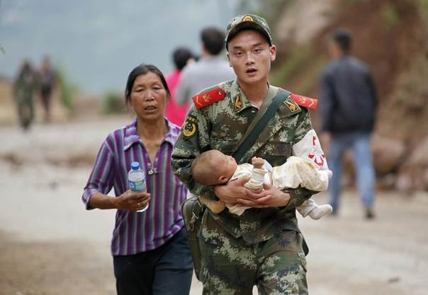 A paramilitary policeman carries a baby after an earthquake hit Ludian county of Zhaotong, Yunnan province, August 3, 2014. REUTERS/China Daily