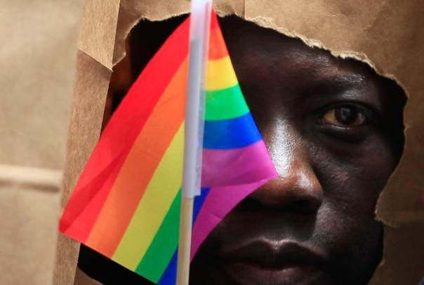 An asylum seeker from Uganda covers his face with a paper bag in order to protect his identity as he marches with the LGBT Asylum Support Task Force during the Gay Pride Parade in Boston, Massachusetts, United States, June 8, 2013. REUTERS/Jessica Rinaldi