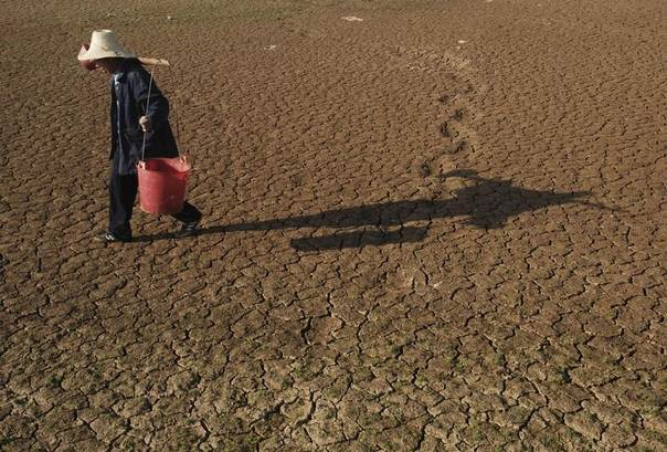 A farmer carries buckets to collect water as he walks on a dried-up pond on the outskirts of Yingtan, Jiangxi province, Nov. 3, 2009. REUTERS/Stringer