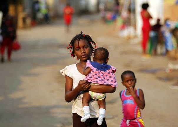 A young girl holds a child as they walk on the streets in Sambizanga informal settlement outside Luanda, Angola,  August 28, 2012. REUTERS/Siphiwe Sibeko