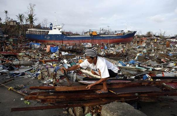 A typhoon survivor retrieves nails from planks to build a makeshift shelter, near a ship that was swept ashore by super Typhoon Haiyan two weeks ago, in Tacloban city, central Philippines November 22, 2013. REUTERS/Erik De Castro