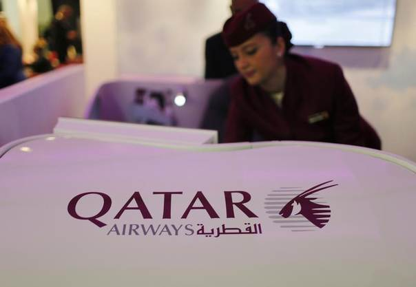 A Qatar Airways flight stewardess shows the airline's new business class seat during the Arabian Travel Market exhibition in Dubai, United Arab Emirates, May 6, 2013. REUTERS/Ahmed Jadallah