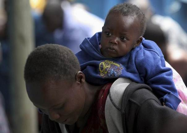 A patient waits for anti-tuberculosis drugs whilst carrying her child at the Blue House clinic, run by medical charity Medecins Sans Frontieres (MSF) in the Mathare valley slums of Kenya's capital Nairobi in this file photo. REUTERS/Thomas Mukoya