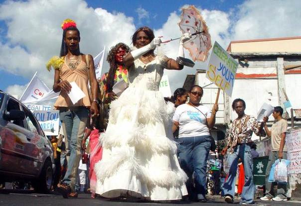 Wearing wigs and in full make-up, men dressed in sequinned dresses, feather boas and high heels lead a march down the busy high street of Rose Hill, Mauritius, May 20, 2006. REUTERS/Jean Alain Laperotine