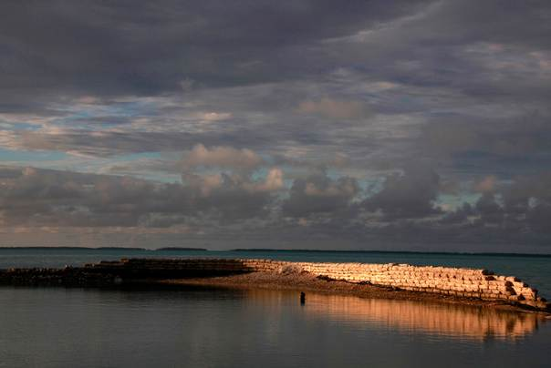 A man swims next to a manmade wall built to protect the island from rising tides near the village of Eita on South Tarawa in the central Pacific island nation of Kiribati on May 25, 2013. REUTERS/David Gray