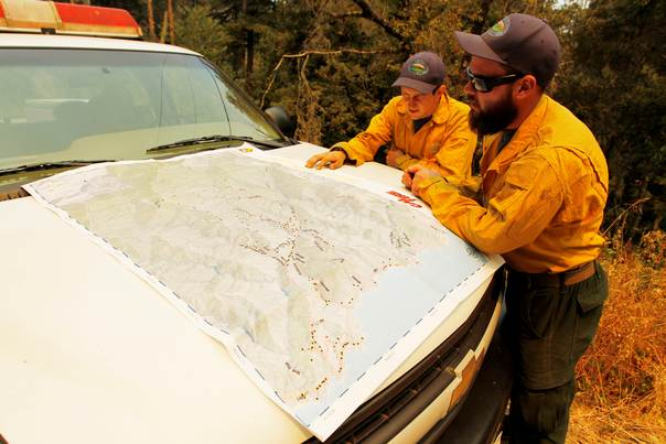 Firefighters Study A Map On The Hood Of A Truck During The Soberanes
