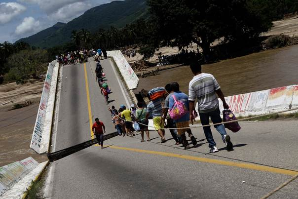 Villagers cross a collapsed bridge in Coyuca de Benitez in the Mexican state of Guerrero, on September 21, 2013. REUTERS/Henry Romero