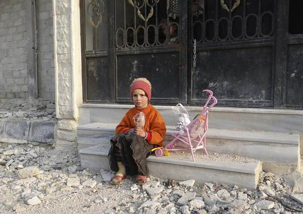 A girl carrying a doll sits on a step of a building as a boy peeks out from its gate in the Damascus suburbs of Arbeen, January 6, 2014. REUTERS/Bassam Al-Erbeeni