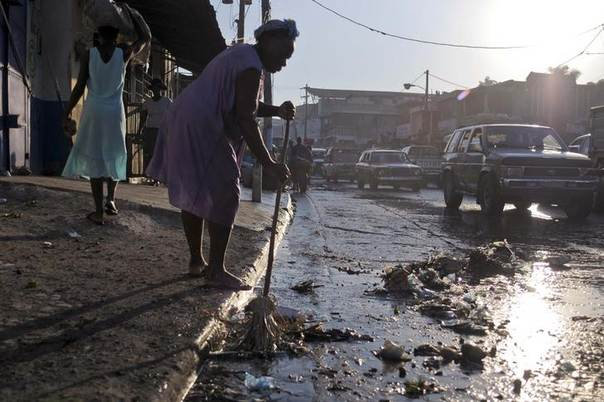 A woman sweeps debris from the sidewalk onto the street, which is frequently flooded, in Port-au-Prince September 4, 2012.  REUTERS/Swoan Parker