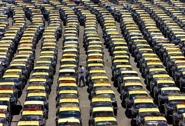 An Indian taxi driver walks amid rows of idle taxis taken off the roads during a one-day strike by the drivers in Bombay April 24, 2002. REUTERS/Arko Datta