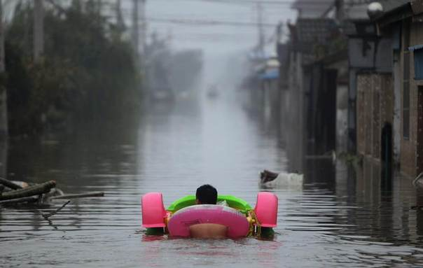 A man pushes a toy boat as he wades down a flooded street with a lifebuoy after Typhoon Fitow hit Tongguang village of Yuyao, Zhejiang province October 9, 2013. REUTERS/China Daily