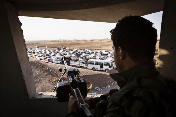 An Iraqi security forces member with his weapon takes position as people, who fled from the violence in Mosul, arrive in their vehicles at a camp for internally displaced people on the outskirts of Arbil in Iraq's Kurdistan region June 14, 2014. REUTERS/Jacob Russell