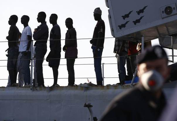 Migrants disembark from a navy ship in the Sicilian harbour of Pozzallo June 30, 2014. REUTERS/Antonio Parrinello
