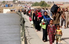 Displaced Iraqis cross the Tigris River, as Iraqi forces battle with Islamic State militants, in western Mosul