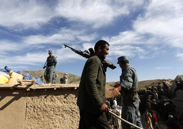 Afghan policemen stand as displaced villagers wait for aid near the site of a landslide at the Argo district in Badakhshan province May 6, 2014. REUTERS/Mohammad Ismail