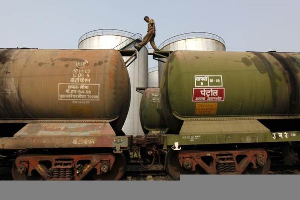 A worker walks atop a tanker wagon to check the freight level at an oil terminal on the outskirts of Kolkata, Nov. 27, 2013. An REUTERS/Rupak De Chowdhuri