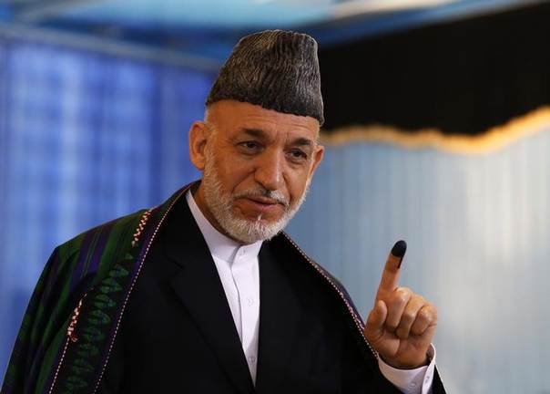 Afghan President Hamid Karzai holds up his ink-stained finger as he leaves after voting in the presidential election in Kabul June 14, 2014. REUTERS/Mohammad Ismail