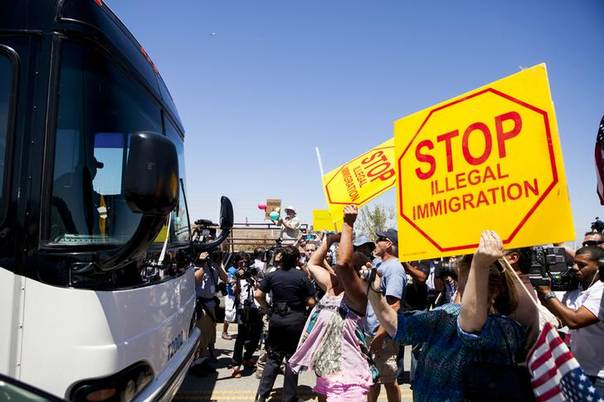 Demonstrators picketing against the arrival of undocumented migrants who were scheduled to be processed at the Murrieta Border Patrol Station block the buses carrying the migrants in Murrieta, California July 1, 2014 REUTERS/Sam Hodgson