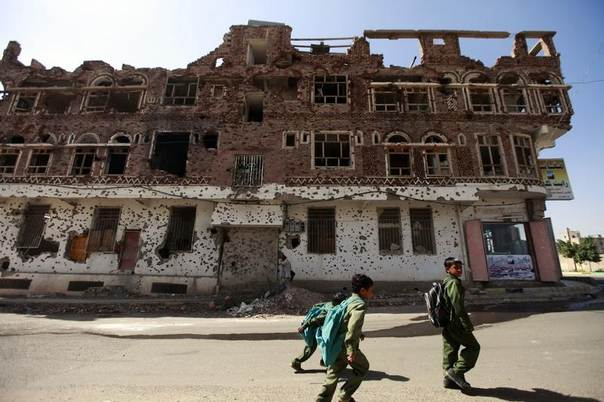 Boys on their way to school walk past a building damaged during protests and clashes in 2011 in Sanaa, Yemen, December 17, 2013. REUTERS/Mohamed al-Sayaghi