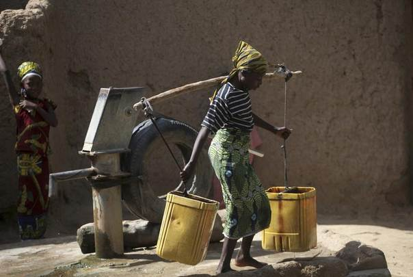 A girl transports water after fetching from a borehole in Bichi village, on the outskirts of Nigeria's northern city of Kano, July 25, 2012.REUTERS/Akintunde Akinleye