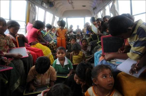 Children with chalkboards attend a class inside a bus converted into a mobile