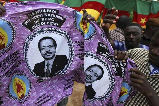 This Oct 7, 2011 photo shows people holding a piece of cloth with pictures of Cameroon's President Paul Biya, near a street stall at the Carrefour Wada district in the capital Yaounde. REUTERS/Akintunde Akinleye