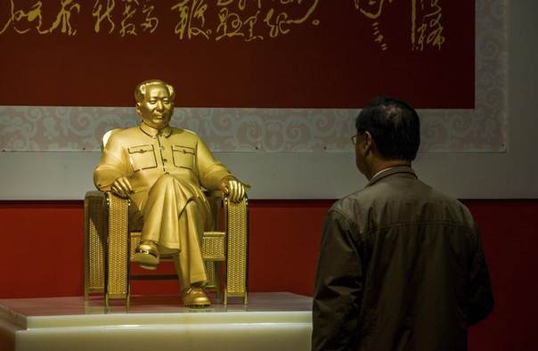 A visitor stands in front of a statue of China's late Chairman Mao Zedong made of gold, jadeite and diamond during an exhibition in Shenzhen, Guangdong province, December 13, 2013 REUTERS/Stringer
