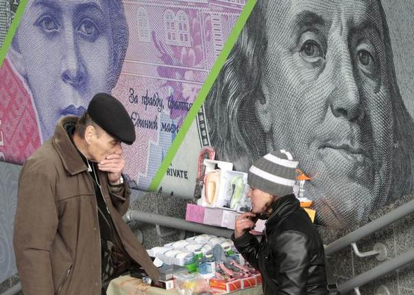 In this 2012 file photo, a customer and street vendor are seen before the background of an outdoor ad with an image of the Ukrainian hryvnia and U.S. dollar bank notes in central Kiev REUTERS/Anatolii Stepanov