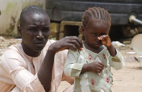 A girl rubs her eye beside her father in an internally displaced persons (IDP) camp, that was set up for Nigerians fleeing the violence committed against them by Boko Haram militants, at Wurojuli, Gombe State, September 1, 2014. REUTERS/Samuel Ini