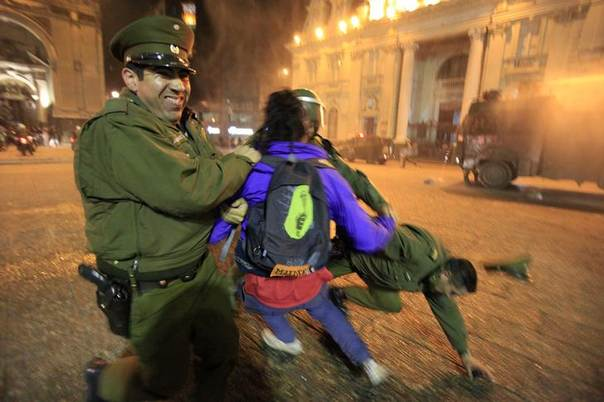 A pro-abortion activist is detained during a rally in Santiago, Chile, held to demand that abortion be