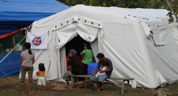 Patients and their families at a Philippine Red Cross medical tent in the grounds of the ruined Loon community hospital. Nichola Jones/IFRC