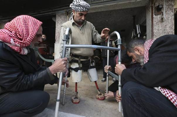 Abu Mazen, a 40 year-old man who lost both his legs during shelling by forces loyal to Syria's President Bashar al-Assad, tries on prosthetic legs at Duma Charity Foundation for Prosthesis in the Duma neighbourhood in Damascus February 25, 2014.  REUTERS/Bassam Khabieh