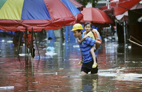 A man carries a girl on his back as he wades through a flooded street after heavy rainfall in Changsha, Hunan province, China, June 20, 2014. REUTERS/Stringer