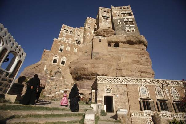 Women walk outside Dar al-Hajar (Rock Palace), one of Yemen's most famous monuments, standing atop a rock hill in a valley 15 km (9 miles) northwest of capital Sanaa, October 16, 2013. REUTERS/Khaled Abdullah