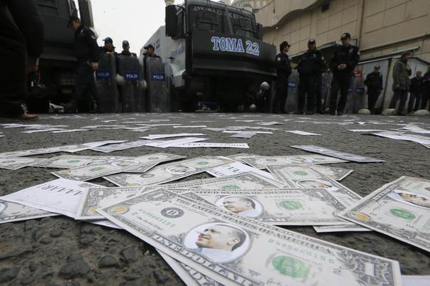 Riot police secure an area as fake U.S. dollar notes with the image of Turkey's Prime Minister Tayyip Erdogan are seen spread across a road leading to a building belonging to the ruling AK Party (AKP) during a protest against Erdogan and his government in Ankara, Turkey, February 28, 2014. REUTERS/Umit Bektas
