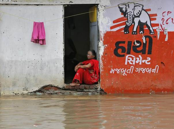 A resident sits at the entrance of her flooded house after heavy monsoon rains in the western Indian city of Ahmedabad July 31, 2014. REUTERS/Amit Dave