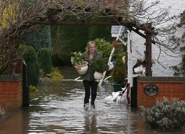 A woman carries belongings outside a flooded house, close to the River Trent in Willington, central England, Nov. 26, 2012. REUTERS/Darren Staples