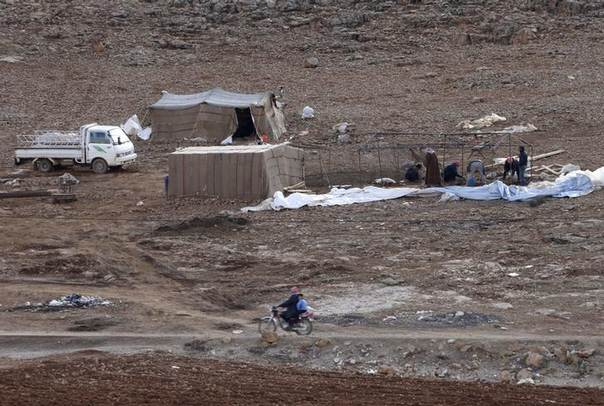 Syrian refugees, who fled the violence from their country, build a tent in preparation for a storm at the Lebanese border town of Arsal, in the eastern Bekaa Valley December 10, 2013.REUTERS/Mohamed Azakir