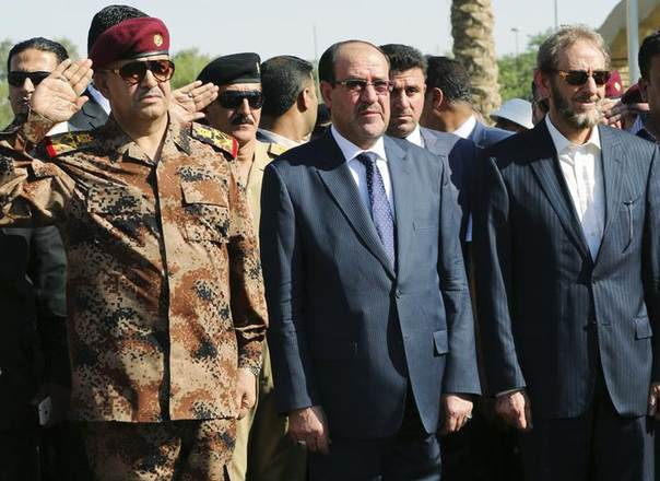 Iraq's Prime Minister Nuri al-Maliki (C) and acting Defence Minister Saadoun al-Dulaimi (R) attend the funeral ceremony of Major General Negm Abdullah Ali, commander of the army's sixth division, at the defence ministry in Baghdad July 7, 2014 REUTERS/Stringer
