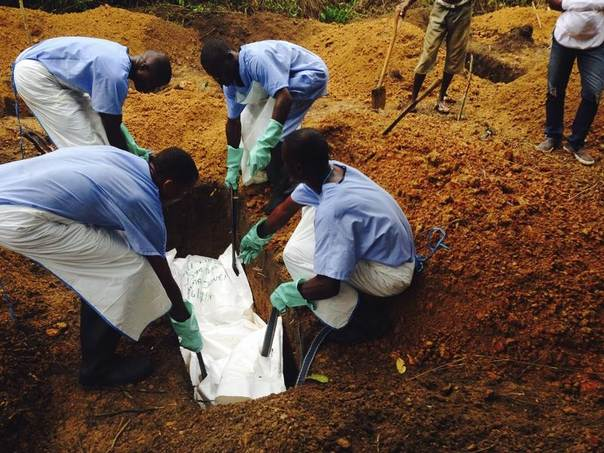 Volunteers lower a corpse, which is prepared with safe burial practices to ensure it does not pose a health risk to others and stop the chain of person-to-person transmission of Ebola, into a grave in Kailahun, Siera Leone, July 18, 2014. REUTERS/WHO/Tarik Jasarevic/Handout via Reuters