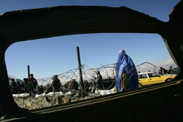 This 2006 file photo shows an Afghan woman standing near an aid distribution table set up by CARE International in Kabul, Afghanistan. REUTERS/Stringer