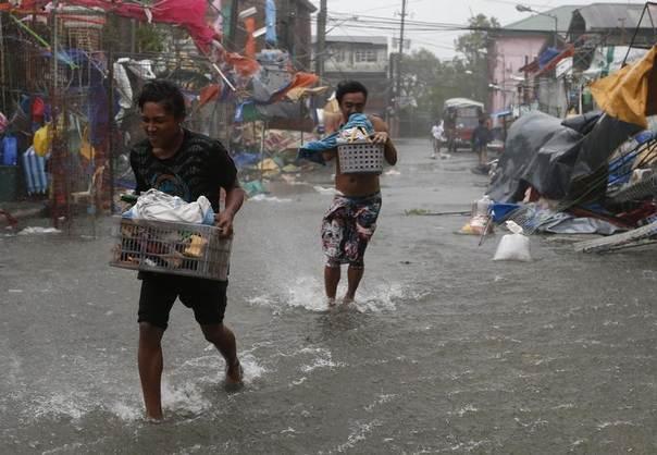 Residents carry their belongings as Typhoon Rammasun hit the town of Imus, Cavite southwest of Manila, July 16, 2014. REUTERS/Erik De Castro