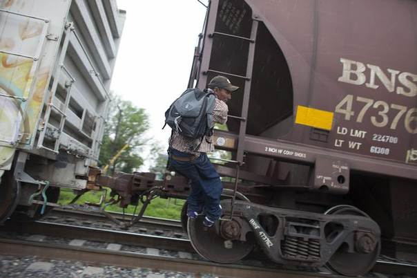 A migrant demonstrates to his friend (not pictured) how to catch a moving train in Atitalaquia, outskirts of Mexico City June 26, 2014 REUTERS/Alexandre Meneghini