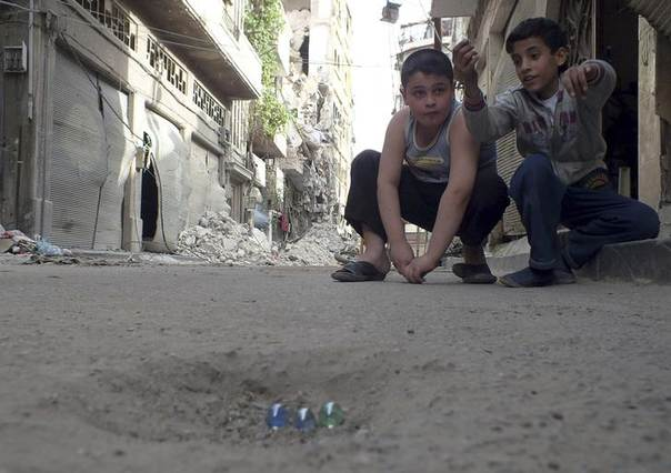 Children play with marbles in a street in the besieged area of Homs May 30, 2013. Picture taken May 30, 2013. REUTERS/Yazan Homsy