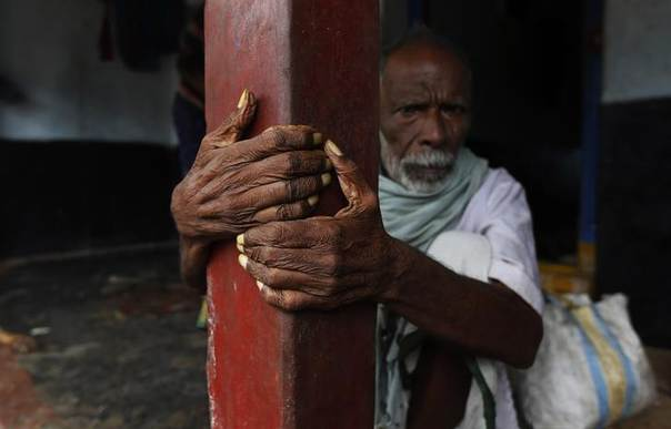 A man sits outside his house as he waits to be evacuated to a safer place at Donkuru village in Srikakulam district, in the southern Indian state of Andhra Pradesh October 12, 2013. REUTERS/Adnan Abidi